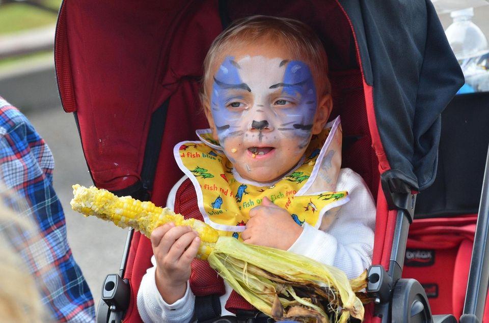 Ethan Craig, 2, from Melville, enjoys corn on