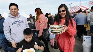 Tina Xing of Jericho carries trays of oysters