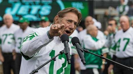 Joe Namath speaks, with members of the team