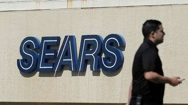 A man walks in front of a Sears