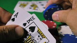 A hand of poker with poker chips.