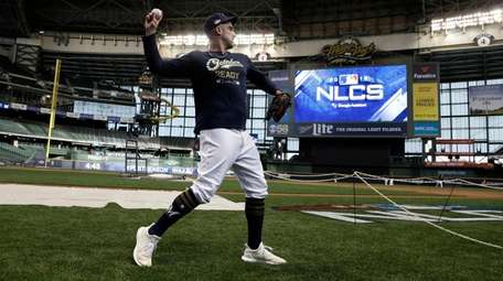 The Brewers' Travis Shaw warms up for practice