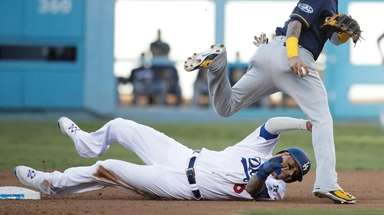 The Brewers' Orlando Arcia leaps over the Dodgers'
