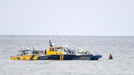 Rescuers search the waters off Quogue on Sunday.