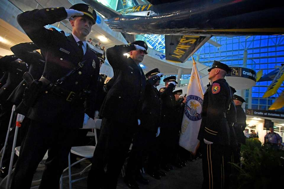 Members of the Nassau County Police Department salute