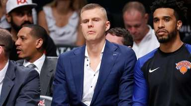 Knicks forward Kristaps Porzingis sits on the bench