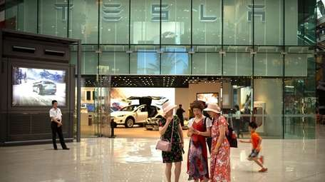 Women outside of a Tesla showroom at an