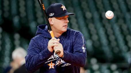Astros manager AJ Hinch hits during batting practice