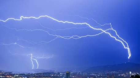 Lightning strikes a tower during a thunderstorm in