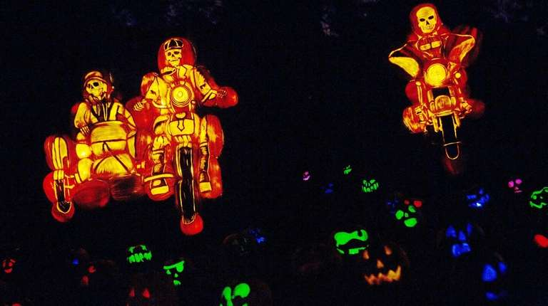 Carved and illuminated Jack o'lanterns line the path