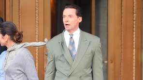 Hugh Jackman rushes out of a building in