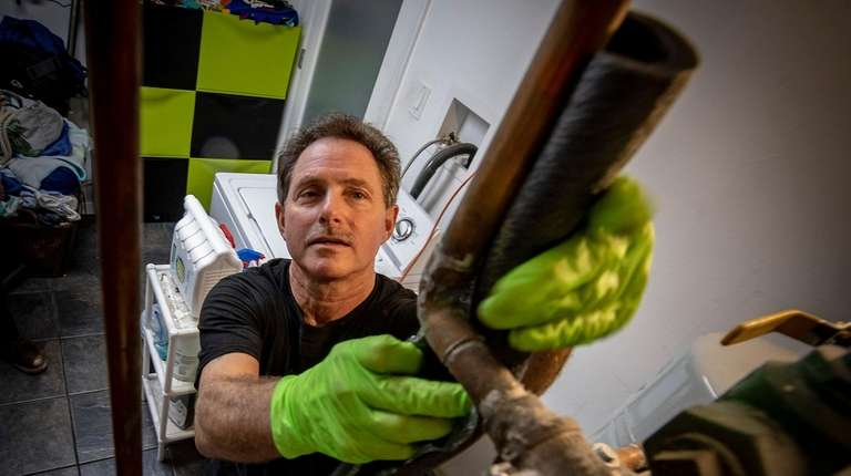Ed Schoen of Prestige Heating Service works on