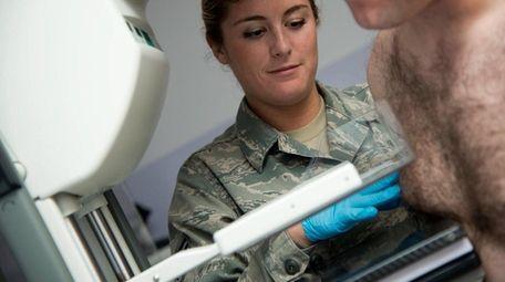 Senior Airman Elisabeth Stone compresses a male patient's
