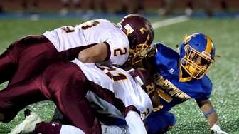 Comsewogue RB Reno Molina is brought down by