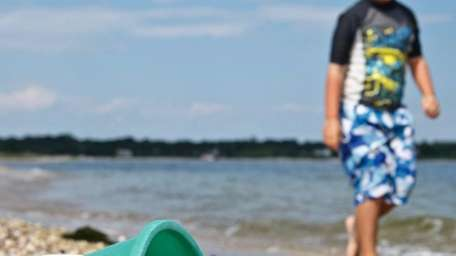 A bucket of seashells lies on Shell Beach