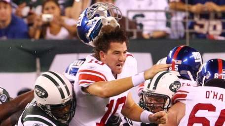 Eli Manning of the Giants loses his helmet