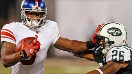 The Giants' Victor Cruz stiff-arms the Jets' Dwight