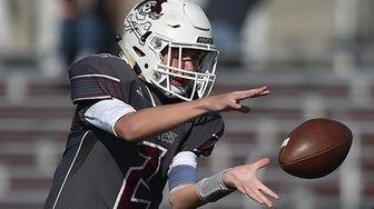 William Kender #2, Mepham quarterback, takes a snap