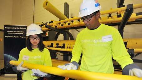 Amanda Low and Shane Parmassar inspect a pipe