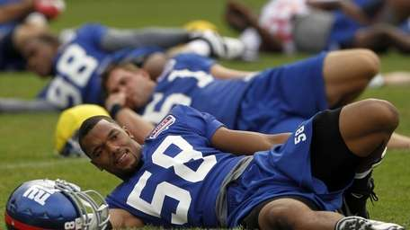New York Giants linebacker Gerris Wilkinson stretches during