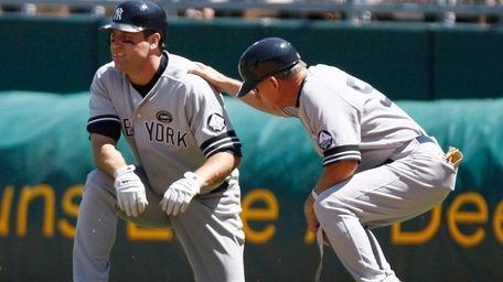 The Yankees' Lance Berkman, left, kneels next to