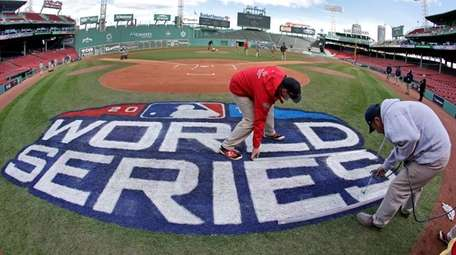 Grounds crew members paint the World Series logo