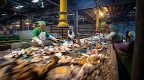 Workers sort recycled material at the Town of