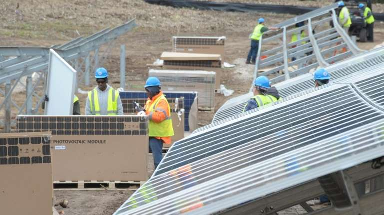 Workers assemble some of the 3,456 individual 320-watt