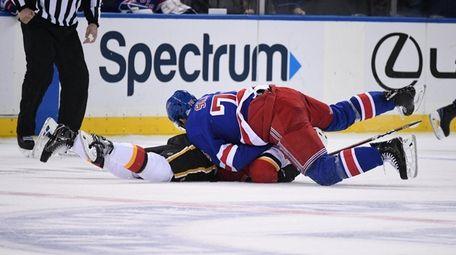 Rangers defenseman Brady Skjei tackles Flames defenseman Rasmus