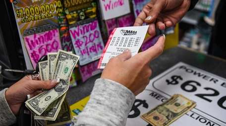 A hopeful customer buys a Mega Millions ticket