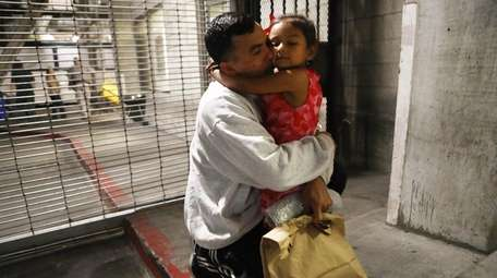 Honduran father Victor hugs his daughter Katie outside