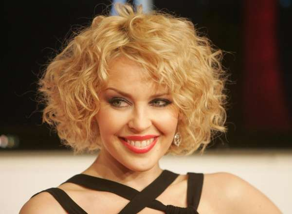 Australian singer Kylie Minogue poses for photographers as