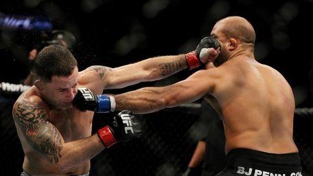 Frankie Edgar, left, and BJ Penn exchange punches