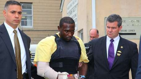 Darrell Fuller, center, leaves Nassau police headquarters in