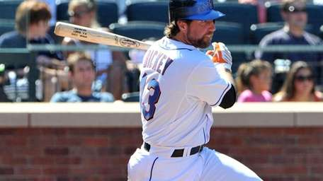 The Mets' R.A. Dickey hits a single in
