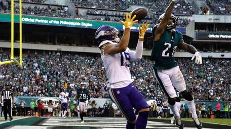 Adam Thielen catches a touchdown pass during the