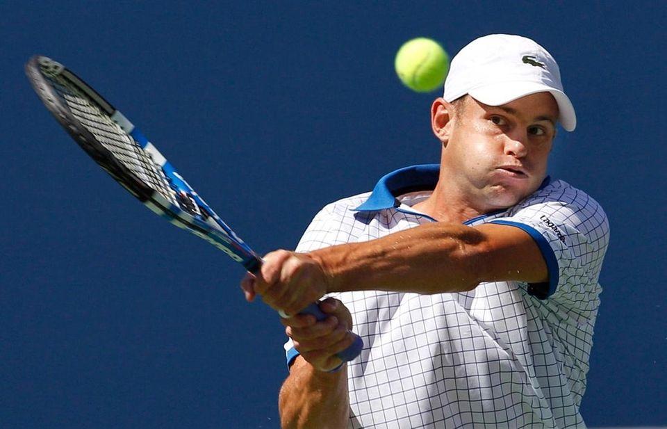 Andy Roddick returns a shot to Stephane Robert