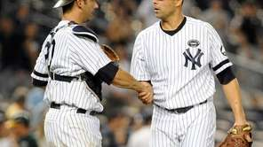 Jorge Posada, left, congratulates Javier Vazquez after the