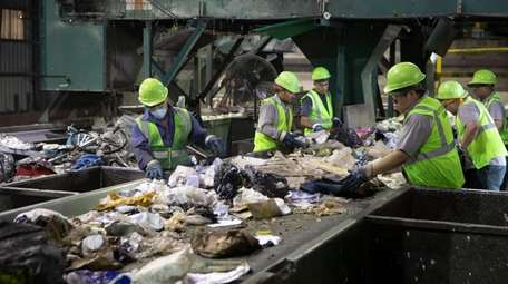 Workers sort commercial recycled material at the Winter