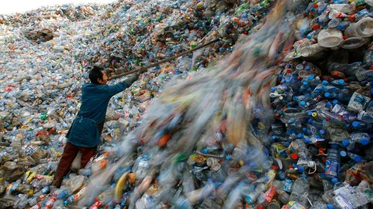 A worker sorts plastic bottles at a recycling