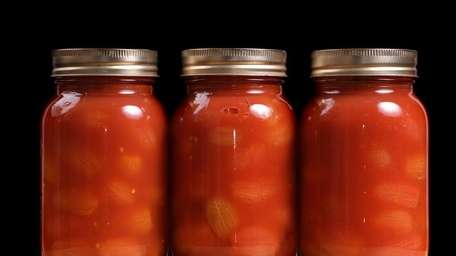Home-canned tomatoes are placed in a row for