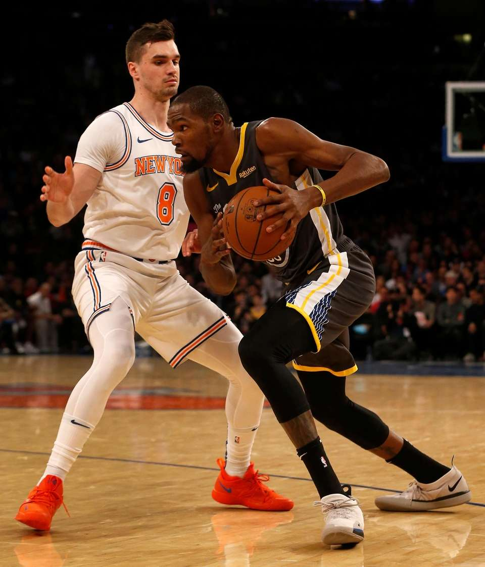 The Warriors' Kevin Durant drives against the Knicks'