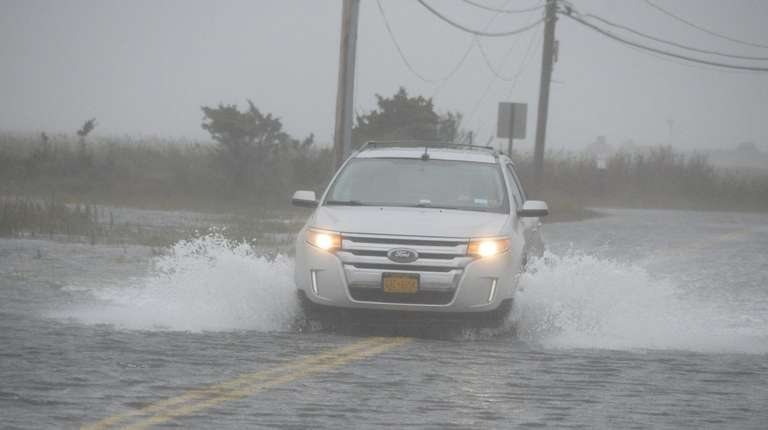 A car makes its way down a flooded