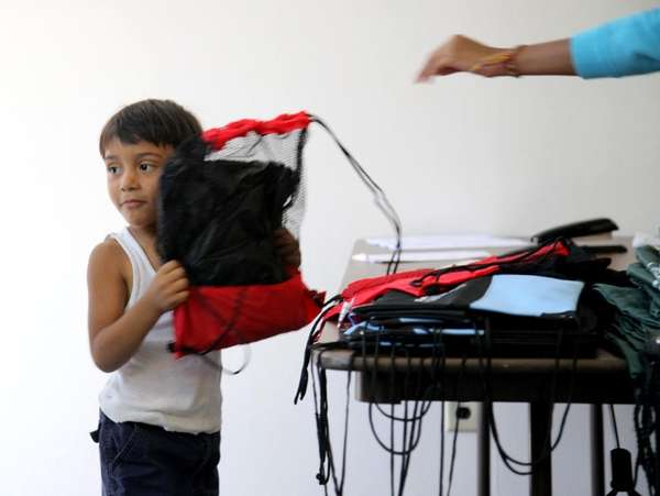 Jonathan Solis, 3, holds his new school supplies