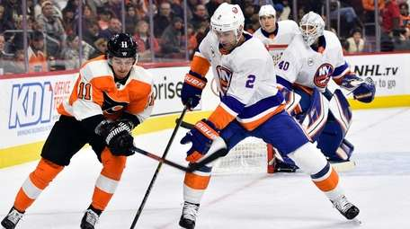 Philadelphia Flyers' Travis Konecny battles New York Islanders'