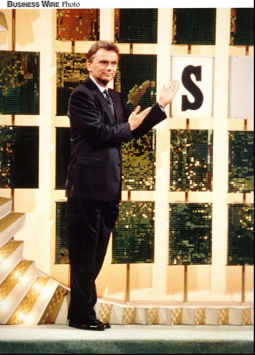 Pat Sajak turns the letters while Vanna White