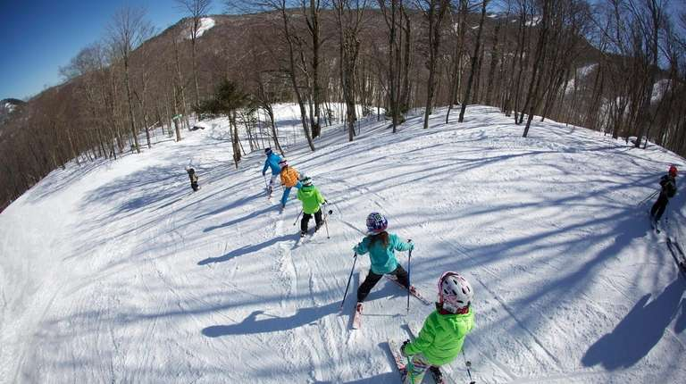 A teacher leads a group of ski schoolers
