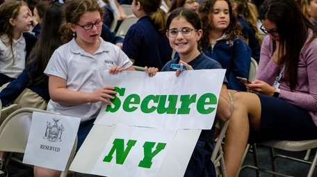 Students display signs as Gov. Andrew M. Cuomo