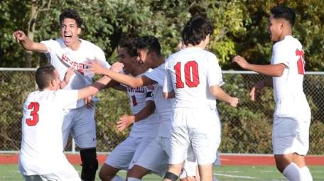 The Newfield boys soccer team celebrates after scoring
