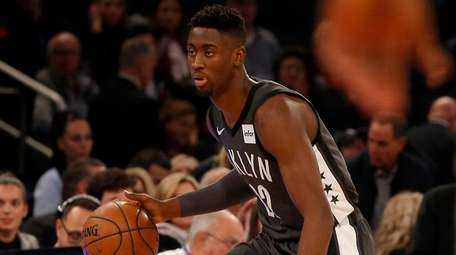 The Nets' Caris LeVert controls the ball during